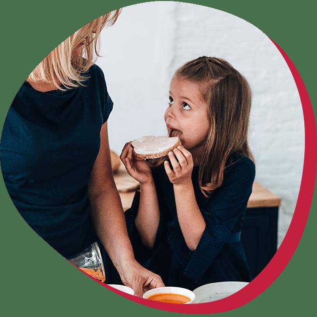 Kind eet boterham en kijkt naar mama